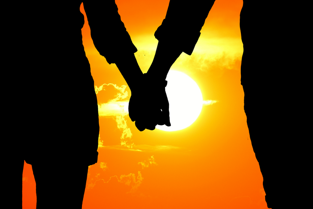 Couple holding hands in the sunset - How to date a woman who travels