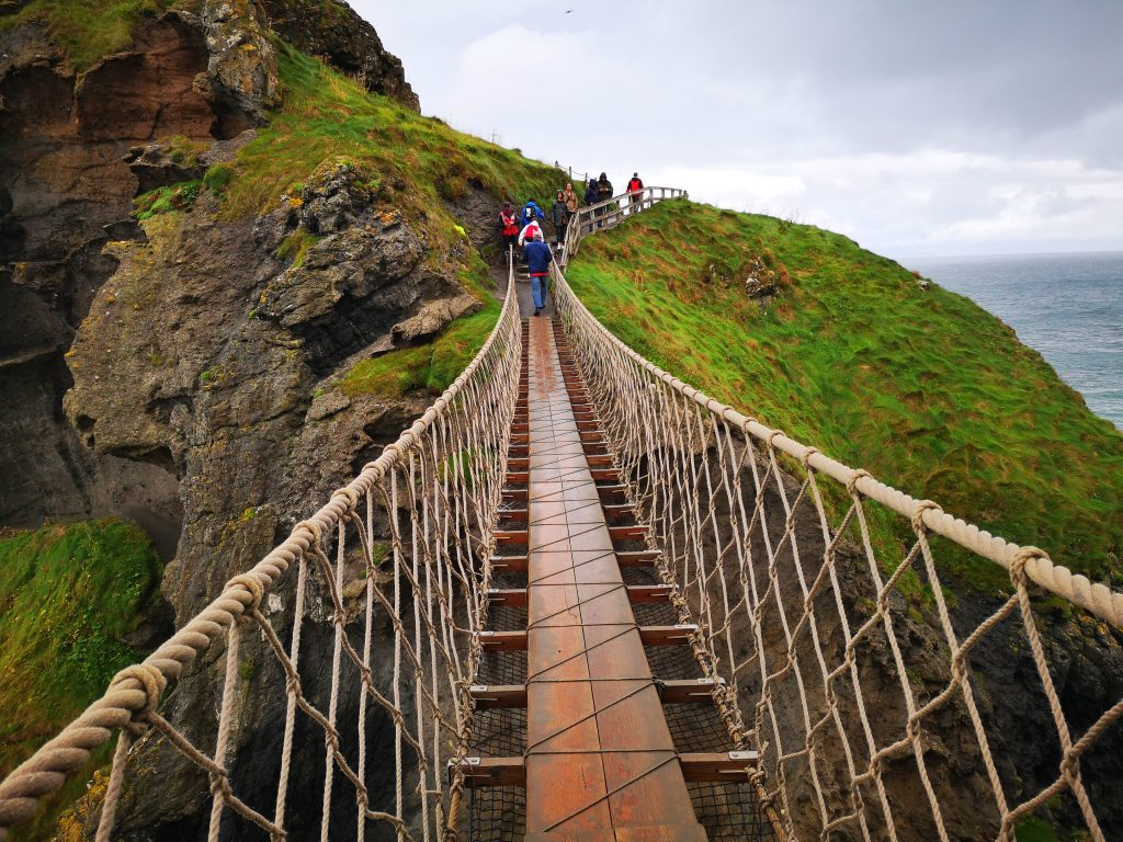 Crossing the Carrick-A-Rede Rope Bridge on our Giant's Causeway Tour from Belfast