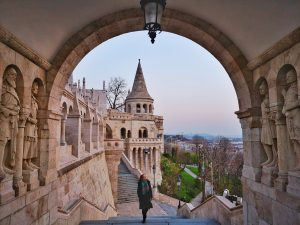 Fishermen's Bastion at Sunrise - Claire Walking Through an Archway with a tower in the background- Budapest on a Budget