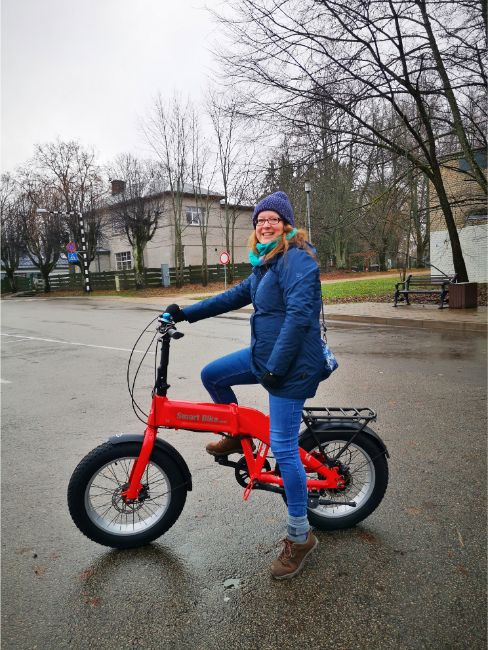 Exploring Sigulda on an E-Bike - Me Sitting on a Red ebike with a blue coat and woolly hat