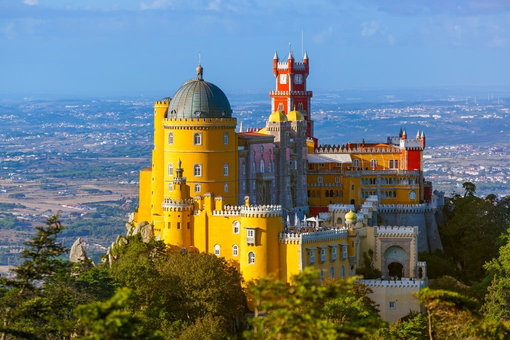 Castles in Sintra - Pena Palace and Park - yellow and red turrets of the castle on a hill surrounded by views of the countryside