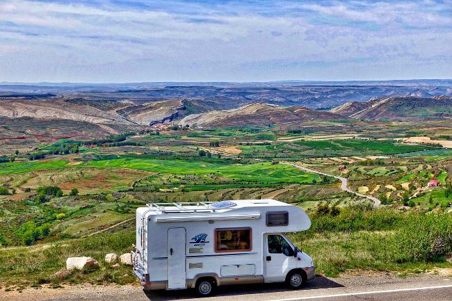 Motorhome on a road with a great view of fields and hills in the background -Being Prepared Gives you More Freedom to Enjoy your Campervan Adventure
