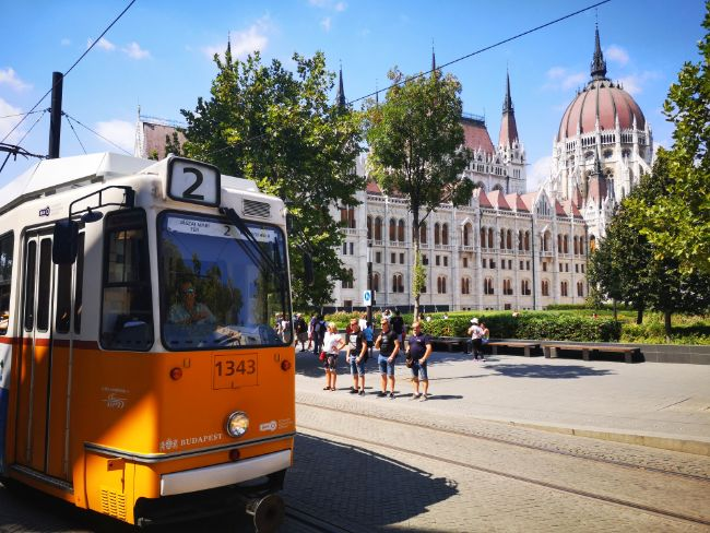 Yellow Tram in front of the Budapest Parliament building - Trams in Budapest are Cheap and Scenic too - Cheap Things to do in Budapest
