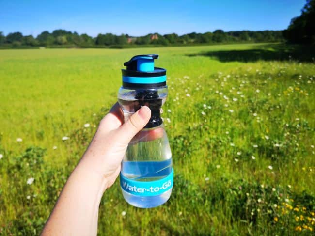 Hand holding a Water-To-Go Bottle with a green field in the background