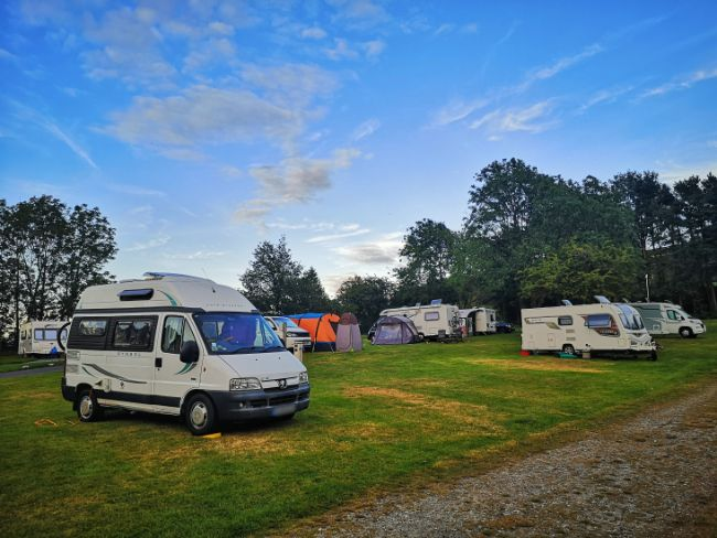 Mabel the Motorhome parked on grass with other caravans and campervans around her - Even if Campsites are Busy, Campers are Usually Really Friendly